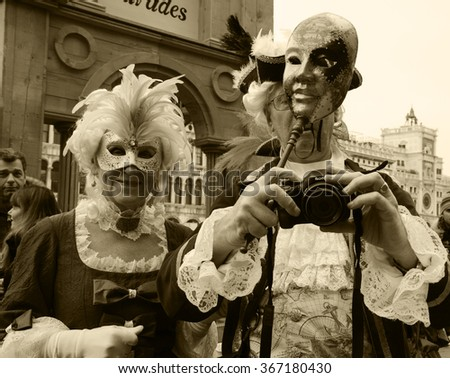VENICE, ITALY - FEBRUARY 14, 2015: Two seniors in masks taking photo at St Mark's Square during traditional Carnival. The Carnival in Venice is annual event which ends on Shrove Tuesday. - stock photo
