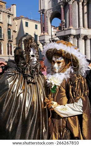 VENICE, ITALY - FEBRUARY 8, 2015: Two unidentified masked persons in golden costume on San Marco Square during the Carnival in Venice, Italy. Vertical image - stock photo