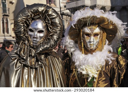 VENICE, ITALY - FEBRUARY 8, 2015: Two unidentified masked persons in golden costume on San Marco Square during the Carnival in Venice, Italy.  - stock photo