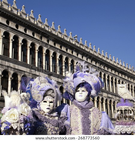 VENICE, ITALY - FEBRUARY 8, 2015: Two unidentified masked persons in ornate lilac medieval costume on San Marco Square during the Carnival in Venice, Italy. Square image - stock photo