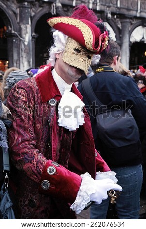 VENICE, ITALY - FEBRUARY 8, 2015:Unidentified masked person in costume on San Marco Square during the Carnival in Venice, Italy. - stock photo
