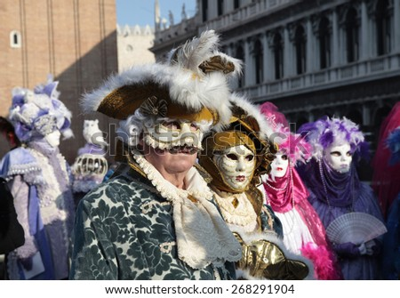 VENICE, ITALY - FEBRUARY 8, 2015: Unidentified masked persons in beautiful medieval costume on San Marco Square during the Carnival in Venice, Italy. - stock photo