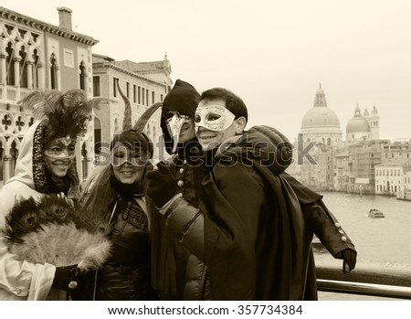 VENICE, ITALY - FEBRUARY 14, 2015: Unidentified tourists in masks being photographed at Accademia bridge with a view on Grand Canal and Basilica Santa Maria della Salute during the Carnival in Venice. - stock photo