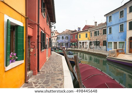 VENICE, ITALY - FEBRUARY 09, 2016: wide view on colorful houses from a secondary street in Burano island during a cloudy winter day