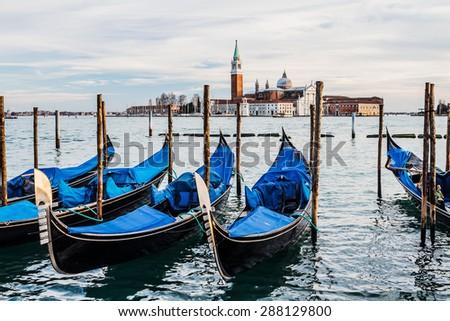 VENICE, ITALY - JANUARY 31, 2015: Gondolas in Venice and San Giorgio island - stock photo