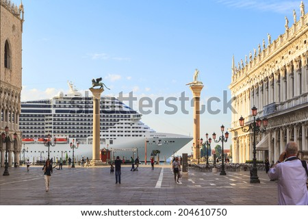 VENICE, ITALY - JUN 9: Tourists enjoy sightseeing in St. Mark's Square in the morning while a cruse liner just arrive on Jun 9, 2014 in Venice, Italy. St. Mark's Basilica is nearly 1000 years old  - stock photo