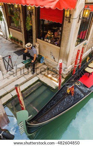 VENICE, ITALY - 26 JUNE, 2014: Gondolier on the pier. The profession of gondolier is controlled by a guild, which issues a limited number of licenses