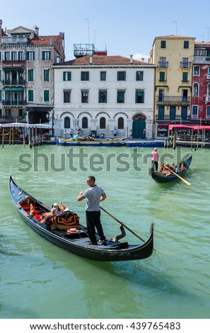 VENICE, ITALY - 26 JUNE, 2014: Gondolier rides gondola. The profession of gondolier is controlled by a guild, which issues a limited number of licenses