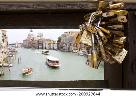 VENICE, ITALY- JUNE 15,2014: Locks on bridge above Grand Canal in Venice, Italy on June 15, 2014. Grand Canal is lined with more than 170 buildings, most which date from the 13th to the 18th century. - stock photo