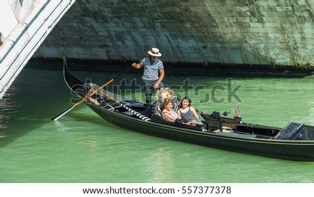 VENICE, ITALY - JUNE 26, 2014: Tourists float in gondola on canal in Venice