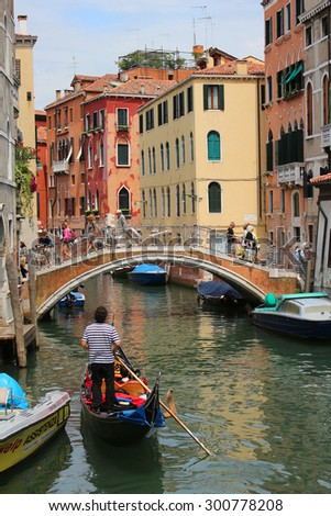 VENICE, ITALY, JUNE 23, 2015: Tourists take a gondola ride  through a busy canal with colorful houses of Venice, Italy - stock photo