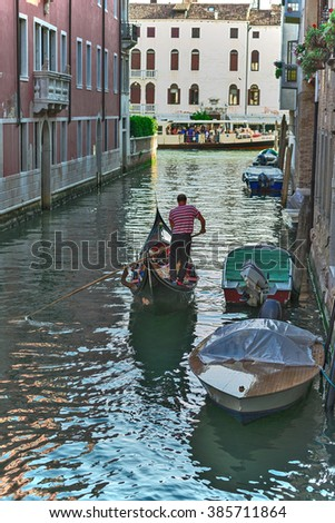 VENICE, ITALY - JUNE 26, 2014: Tourists travel on gondolas at canal Venice, Italy . Gondola trip is the most popular touristic activity in Venice. - stock photo