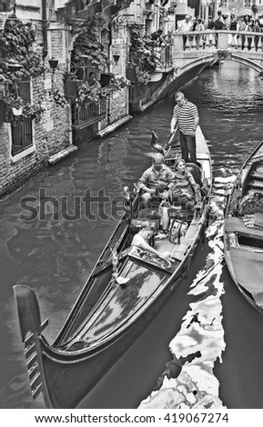 VENICE, ITALY - JUNE 26, 2014: Tourists travel on gondolas at canal Venice, Italy . Gondola trip is the most popular touristic activity in Venice. Old-style, black - white photo.