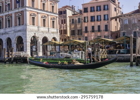 VENICE, ITALY - JUNE 30, 2015: View from Grand Canal on gondolier and tourists and old surrounding multicolored buildings, colored photo.