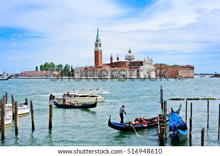 VENICE, ITALY - JUNE 14, 2016:  Water taxi's and Gondola's are busy in the harbor near St. Marks Square, with Church of San Giorgio Maggiore in the background.