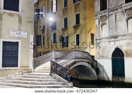 VENICE, ITALY - MARCH 31, 2016: An arch bridge with decorative railings and marble steps over a canal in Venice, illuminated in the night and surrounded by color buildings.