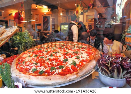 VENICE, ITALY - MARCH 04, 201: Big pizza with red tomatoes and cheese displayed on restaurant window and visitors inside on background. Pizza is traditional italian dish very popular around the world. - stock photo