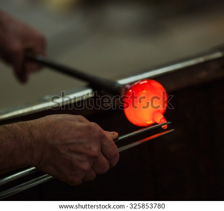 VENICE, ITALY - MARCH 22, 2015: Glass blower at work shaping molten glass, Murano, Venice, Italy (selective focus) - stock photo