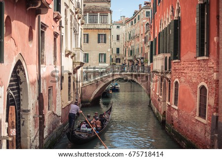 VENICE, ITALY - MAY 8, 2017: Boats on a small canal with bridges in the heart of Venice.