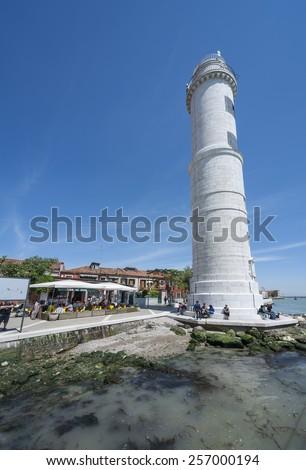 Venice, Italy - May 8, 2014: Lighthouse on Murano island in Venice, Italy. Murano is  well known immaculate glass art work. For visitors to Venice, it is a well known and visited destination. - stock photo