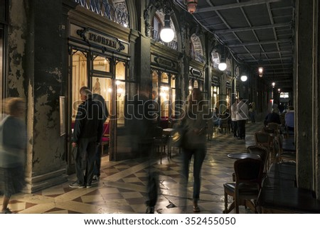 VENICE, ITALY - MAY 29, 2015: The oldest coffee house Florian in Piazza San Marco in Venice at night. Tourists wandering around, some of them in motion blur, some exploring cafe menu.  - stock photo