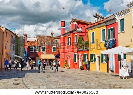 VENICE, ITALY - 17 OCTOBER 2015: Group of tourists sightseeing in Burano, Venice, Italy photographing the famous colorful fishing houses and shopping in the quaint shops and stores - stock photo