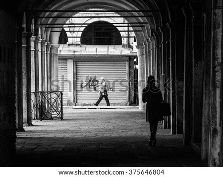 VENICE, ITALY -  14 OCTOBER 2013:  Monochrome image of a woman waiting under an archway as a man walks past.  Contemporary street scenes of Venice, Italy