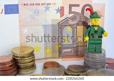 Venice, Italy - October 23, 2014: Robin Hood (as Lego figure) standing on  50 euro bill and European Euro coins, October 23, 2014 in Venice, Italy - stock photo