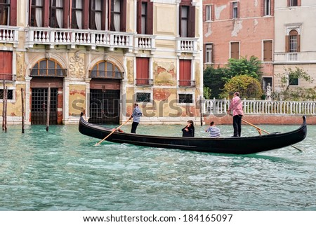 VENICE, ITALY - OCTOBER 26 : Two gondoliers ferrying passengers along the canals of Venice on October 26, 2006. Unidentified people.