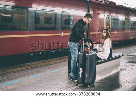VENICE, ITALY - OCTOBER 14, 2015: Young couple sits near the train at St. Lucia railway station in Venice, Italy. Toned picture