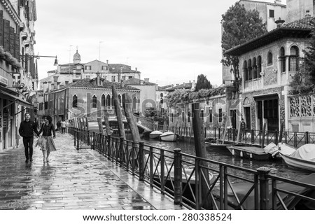 VENICE, ITALY - on APRIL 30, 2015. A typical urban view in rainy weather. Street canal and ancient buildings ashore. Black-and-white image