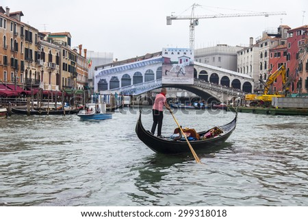 VENICE, ITALY - on MAY 3, 2015. The gondola with passengers floats on the Grand channel (Canal Grande). Restoration of Realto Bridge on a background