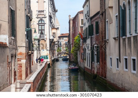 VENICE, ITALY - on MAY 4, 2015. The typical Venetian street canal and its reflection in water