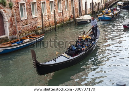 VENICE, ITALY - on MAY 4, 2015. Walk on a gondola on venetian channels  - one of the most known tourist attractions in Venice.