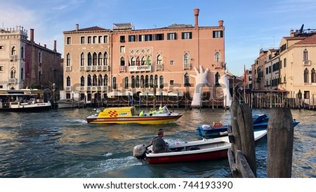 Venice, Italy - September 28, 2017: Boats in front of the famous old buildings and palazzos with hands supporting one palazzo as art installation of the BIennale along the Canale Grande in Venice