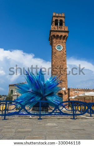VENICE ITALY-SEPTEMBER 3rd 2015: A modern sculpture of Murano glass designed by Master glassmaker and Designer Simone Cenedese in front of the old bell tower of San Giacomo on  Murano island, Venice - stock photo