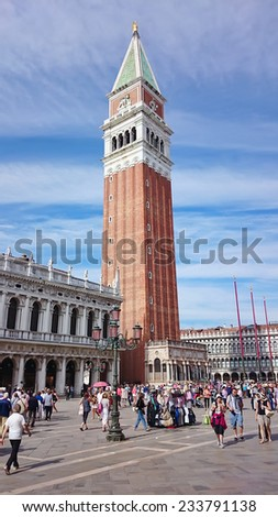VENICE, ITALY - SEPTEMBER 26: Tourists in St Mark's Square or Piazza San Marco with the Campanile or bell tower of St Mark's church and the Logetta at its foot on September 26, 2014 in Venice, Italy. - stock photo