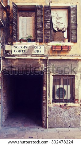 Venice, Italy -This passage under an ancient popular house has an appropriate name,'sottoportego corte scura' , it means 'under passage to the dark yard' - stock photo