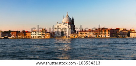 Venice, Italy - view across a wide canal with golden light on an ancient cathedral dome and buildings