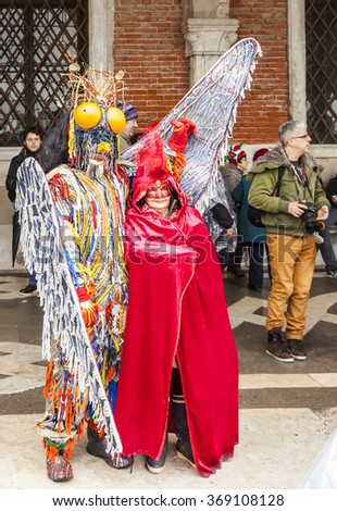 VENICE-MAR 02:Couple disguised in colorful costumes, posing in San Marco Square on March 02,2014 in Venice, Italy, during the Carnival days. - stock photo