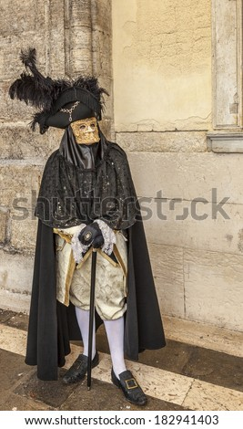 VENICE-MAR 02: Unidentified person specifically disguised wearing a Bauta mask poses near the walls of The Doge's Palace on March 02,2014 in Venice, Italy, during the Carnival days.