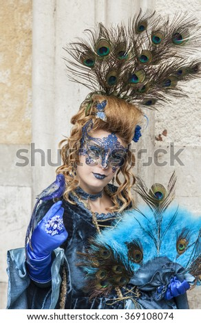 VENICE-MAR 02:Unidentified woman disguised in blue costume with peacock feathers posing in San Marco Square on March 02,2014 in Venice, Italy, during the Carnival days.