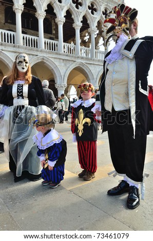 VENICE - MARCH 7: A family masked in costume in St. Mark's Square during the Carnival of Venice on March 7, 2011. The 2011 carnival was held from February 26th to March 8th.