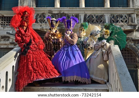 VENICE - MARCH 7: Group of unidentified masked persons in costume on the bridge via water canal during the Carnival of Venice on March 7, 2011 in Venice. - stock photo