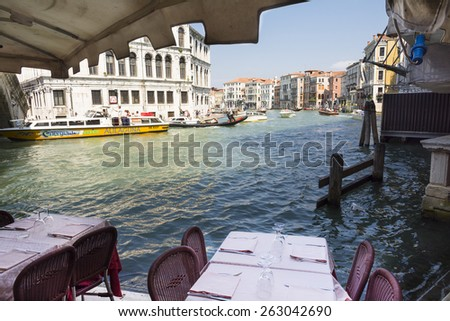 VENICE-MAY 1,2014:tables of a restaurant on the grand canal ready to welcome tourists in front of the Venetian landscape during a sunny day.