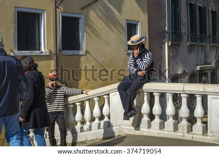 VENICE - OCTOBER 17: gondoliers in traditional dress talking by phones on bridge in Venice, Italy on October 17, 2015. Gondolier is one of the oldest professions in the world controlled by a Guild.