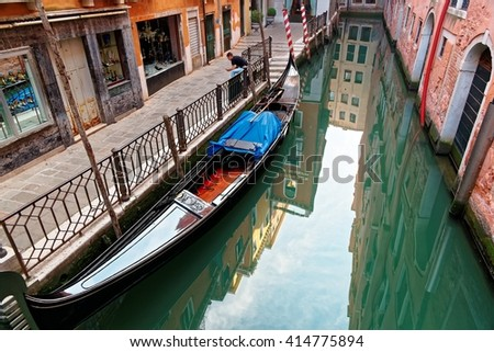 Venice on a peaceful morning, with view of an elegant gondola parking on a narrow canal, a tourist sitting by the quiet alley and reflections of the blue sky and decadent houses on the smooth water - stock photo