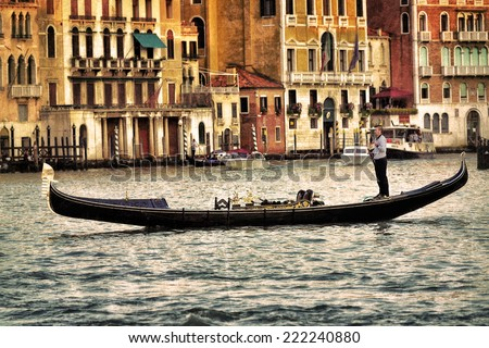 VENICE - SEP 25, 2014: Gondolier rides gondola at sunset on the Grand Canal. Gondola is one of the symbols of Venice and major mode of touristic transport in Venice, Italy.  - stock photo