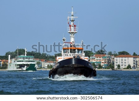Venice, VE - Italy. 14th July, 2015: powerful tugboat used to drive large cruise ships away from the harbor ort of Venice Island across the canale della giudecca