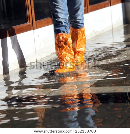 venice woman with orange gaiters at high tide in St. Mark's square